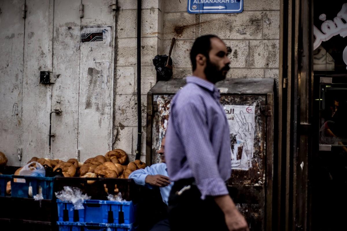 Mężczyzna zmierzający do centrum Ramallah. Za nim widać klasyczny targ z żywnością. Ludzie w trakcie dnia robili zakupy, jednak na spożycie produktów czekali aż do zachodu słońca. Trwał ramadan, podczas którego każdy muzułmanin powyżej 10 roku życia od świtu aż do zmierzchu nie może jeść, pić, palić tytoniu, uprawiać seksu ani używać kosmetyków