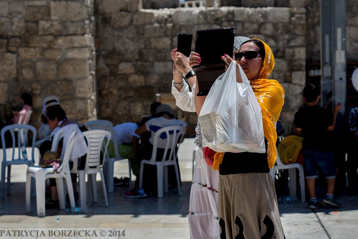 Dwie kobiety muzułmańskie w hidżabie przykrywającym głowę. Obie robią zdjęcia najnowszej generacji iPadami. Zderzenie tradycji z nowoczesnością.