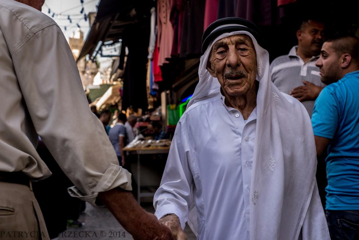Mężczyzna witający się z przyjacielem. Na jego głowie znajduje się kefija, tradycyjne arabskie nakrycie głowy dla mężczyzn. Odmiana palestyńska wykonana zwykle jest z bawełny oraz wełny.