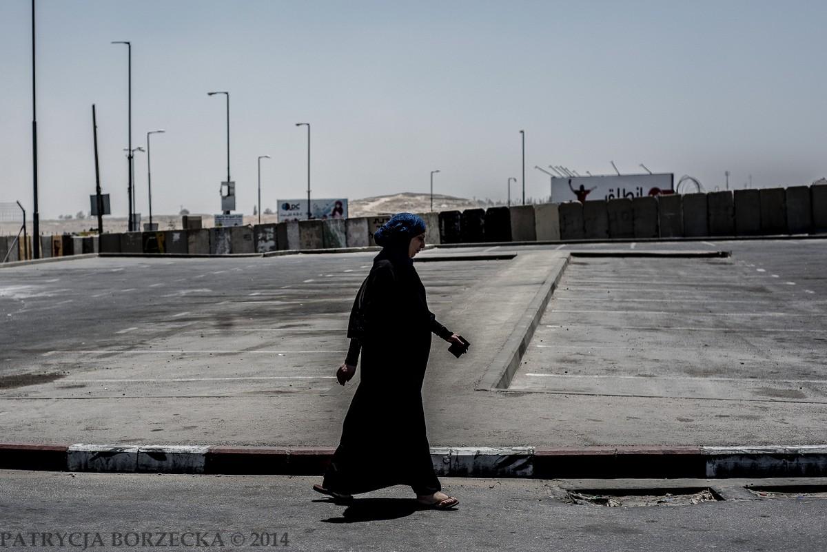 Kobieta palestyńska zmierzała w kierunku punktu kontrolnego. W dłoni trzymała dokumenty, bez których przejście przez granicę jest niemożliwe. W tle - słynny mur odgradzający Izrael od Palestyny.