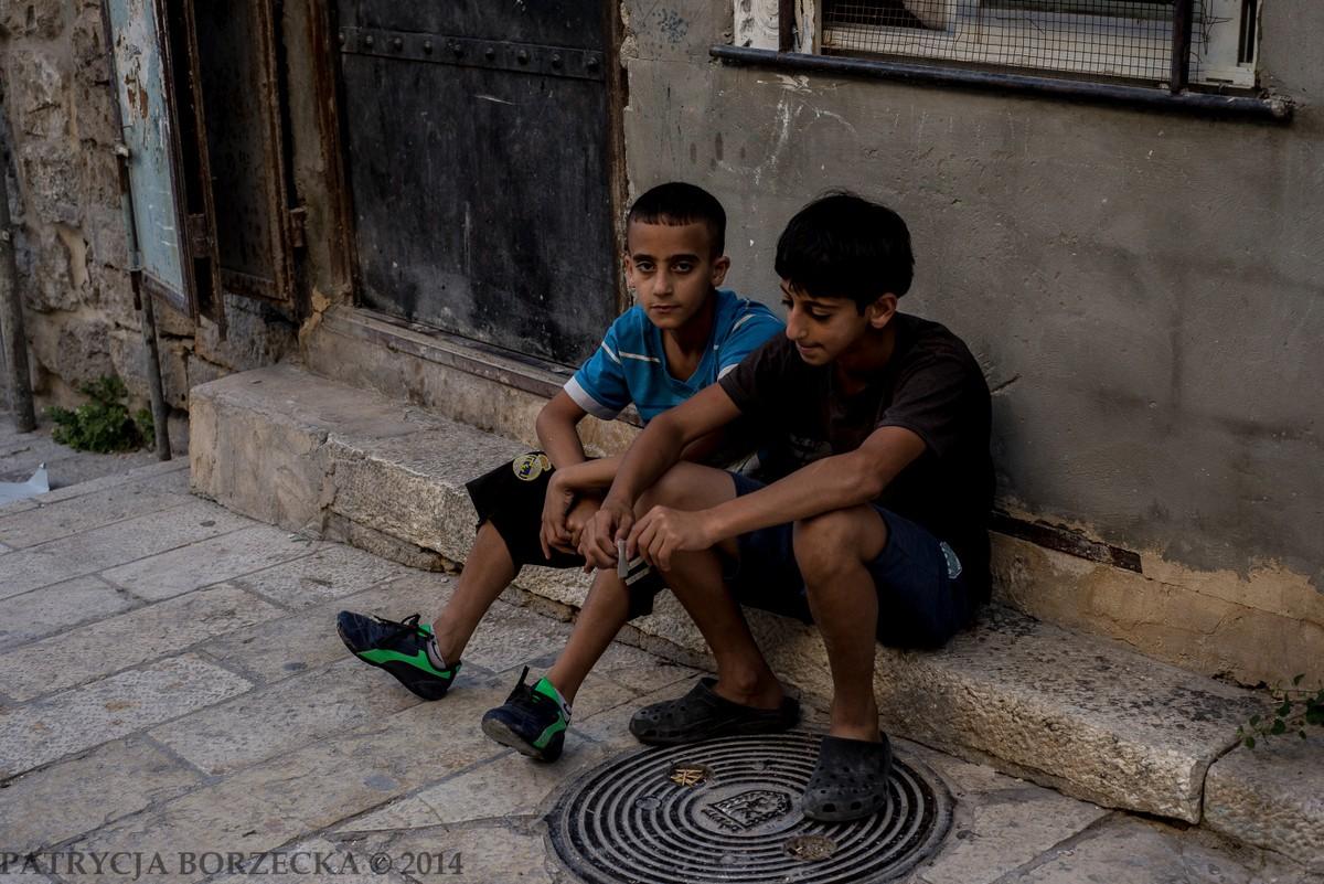 Dzieci palestyńskie w Dzielnicy Muzułmańskiej. Ich zachowanie podkreśla różnice majątkowe pomiędzy Izraelem, a Palestyną. Często proszą o pieniądze albo proponują doprowadzenie do szukanego miejsca w zamian za drobną opłatę.