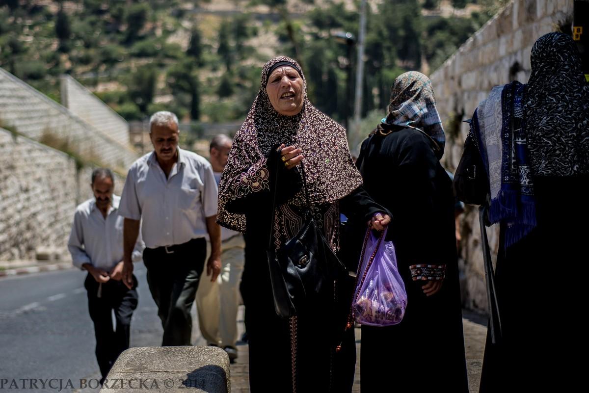 Kobieta muzułmańska w pobliżu drogi prowadzącej na Górę Oliwną. Na jej twarzy malują się liczne emocje. Zdjęcie zostało zrobione w dniu, gdy świat arabski dowiedział się o morderstwie palestyńskiego chłopca, którego spalone ciało pozostawione zostało we Wschodniej Jerozolimie. Mężczyźni idący z tyłu opuszczają głowy. Czuć napięcie.