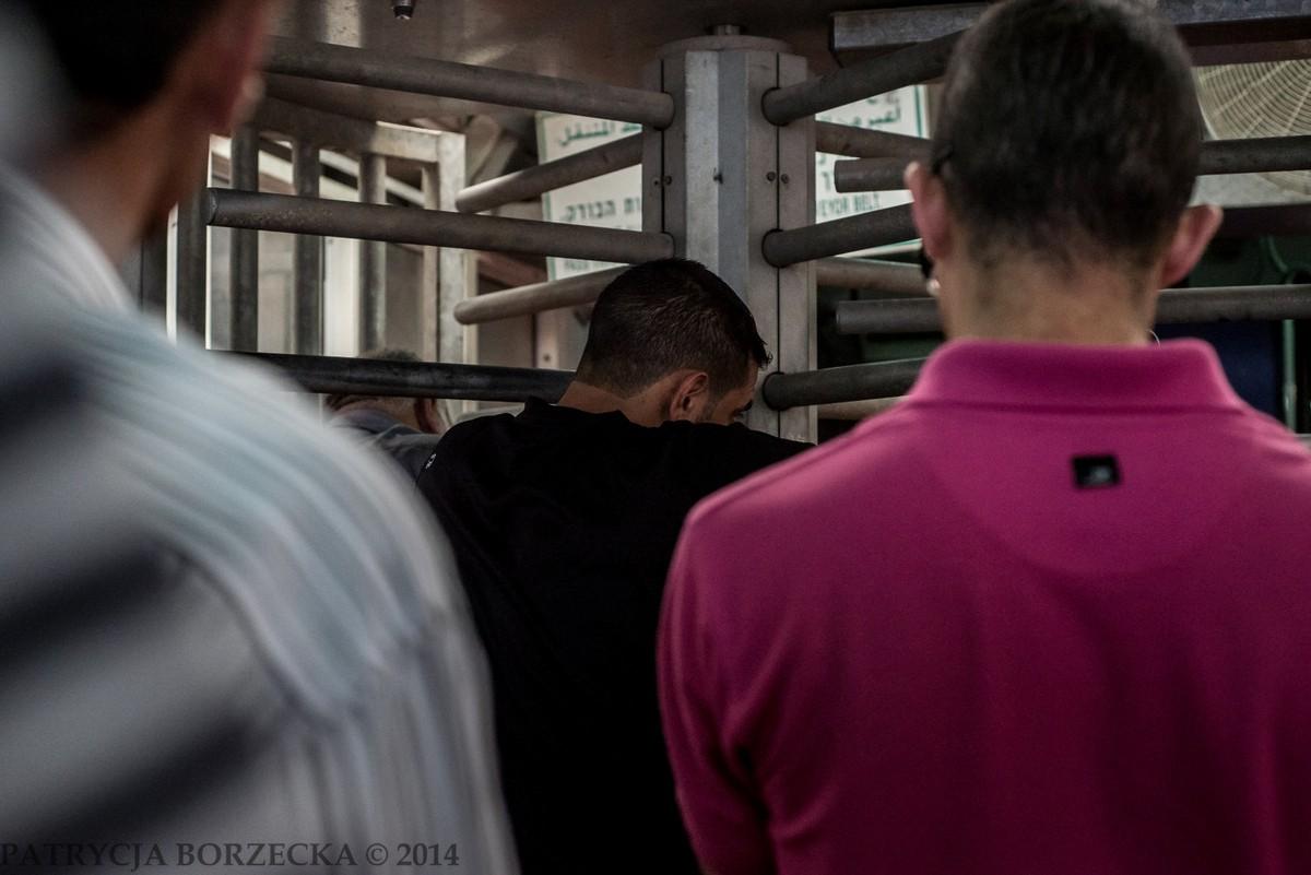 Mężczyźni oczekujący na swoją kolej przejścia przez punkt kontrolny.