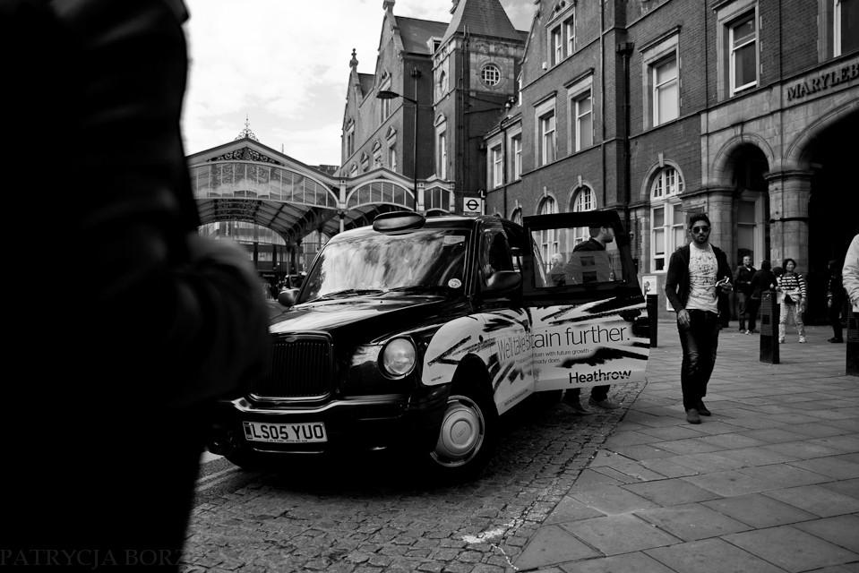 Godzina 13:12. Południe. Mężczyźni w garniturach pędzą do swoich biur. Śpieszą się. Turyści mozolnie wysiadają z taksówek.