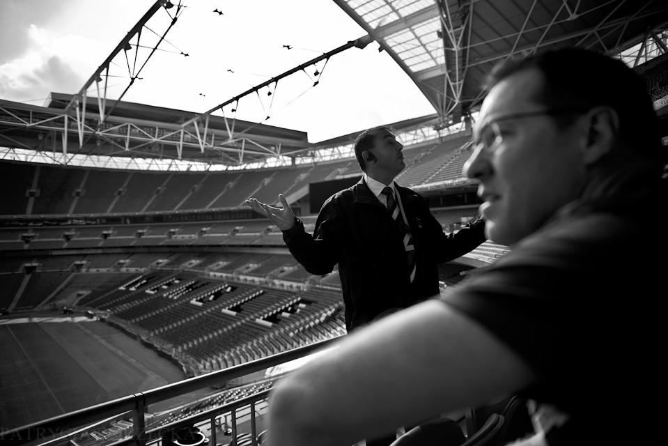 """Godzina 15:17. Przewodnik opowiada historię stadionu Wembley. Zachęca przybyłych turystów do przetestowania jego akustyki.  - Zamilknijcie na chwilę, a potem krzyknijcie głośno """"Hello Wembley!"""""""