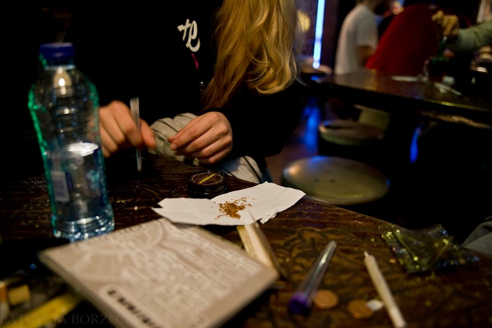 Dziewczyna przygotowuje skręta do spalenia. Obok niej stoi woda. Należy ją zmieszać z cukrem i wypić, jeśli marihuana przyniesie niepożądane skutki.