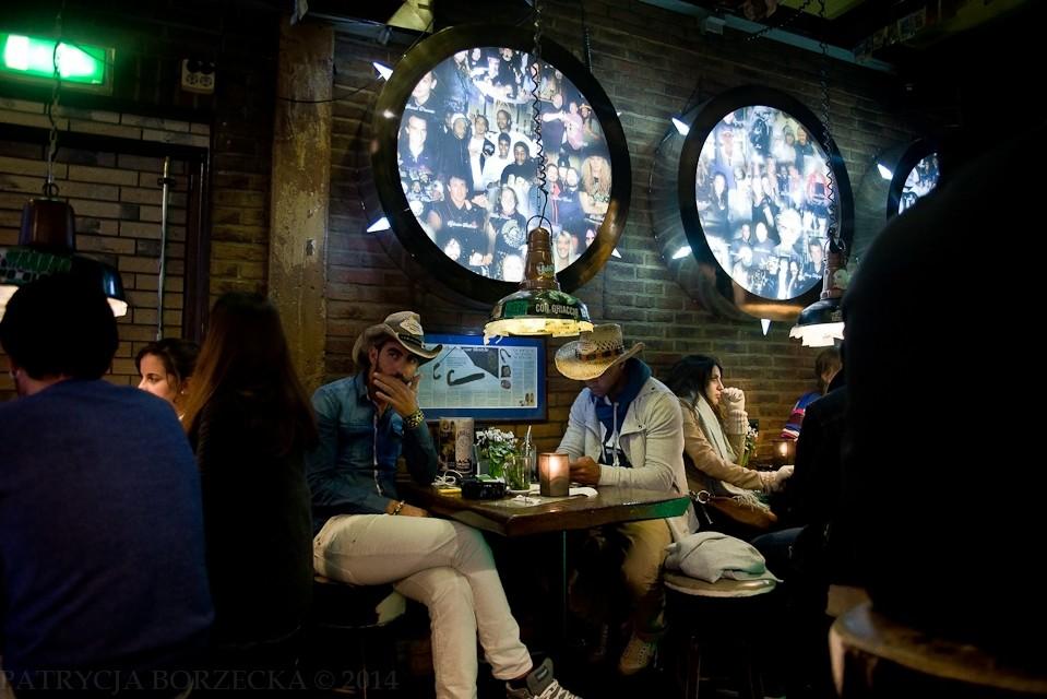 The Bulldog - najsłynniejszy coffee shop w Amsterdamie. Nad głowami mężczyzn w kapeluszach widać mozaiki. Na zdjęciach znajdują się gwiazdy popkultury, które odwiedzały to miejsce - między innymi Rihanna i Britney Spears.