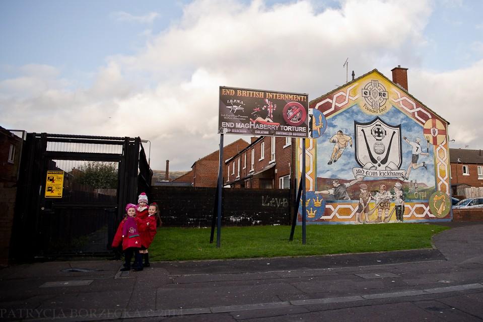 Dzieci uśmiechają się do obiektywu. Obok nich stoi tablica mówiąca o prawie do prywatności i bycia niedyskryminowanym.  Dzieci pomimo młodego wieku są już w pewnym sensie świadome skomplikowanej sytuacji.  Tydzień przed moim przyjazdem do Belfastu protestanckie dzieci obrzuciły kamieniami katolicką szkołę. Wybiły nimi okna.