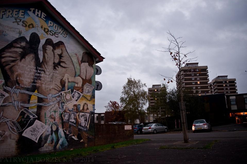 Divis Flats - część Belfastu uznana przez Brytyjczyków za najbardziej niebezpieczną  w całym mieście. Lojaliści w roku 1970 założyli tu swój punkt obserwacyjny. Przejęli dwa najwyższe poziomy Divis Tower i dach budynku. Po lewej stronie widać grafikę ze związanymi dłońmi i napisem ?Free the PoWs?. Słowo ?PoW? to skrót od ?Prisoner of War? (pl: ?więzień wojenny?).