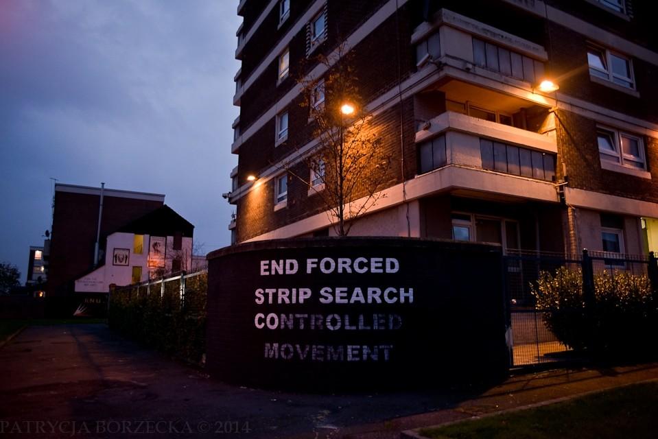 W czasie konfliktu mieszkało tu wielu działaczy IRA. Mieszkańcy Divis Flats byli nieustannie przeszukiwani przez żołnierzy brytyjskich. ?End forced strip search controlled movement? ma charakter symboliczny i oznacza, że w tym miejscu nie będzie już więcej kontroli osobistych i przeszukań.