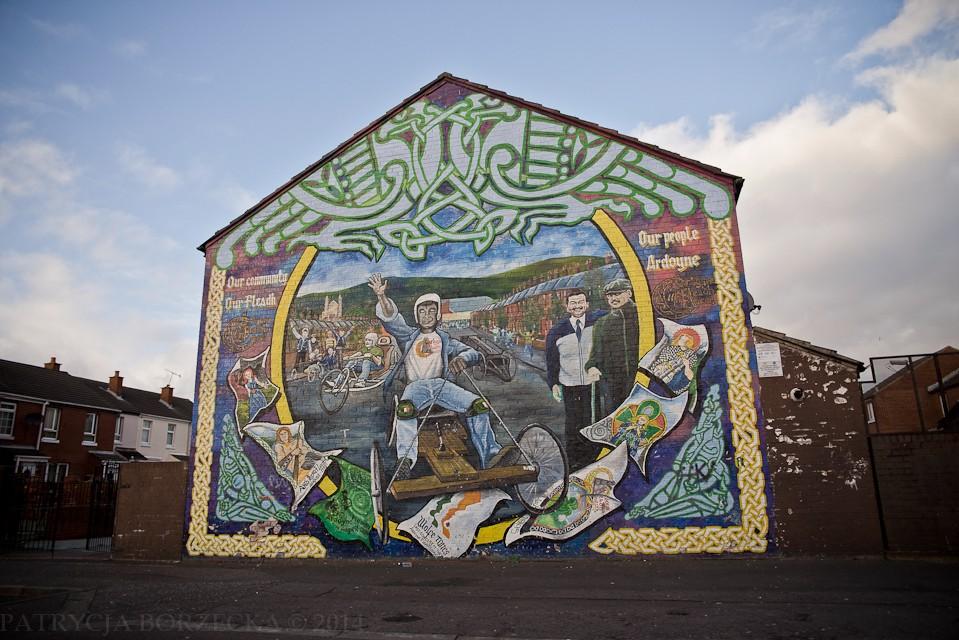 """""""Our people Ardoyne"""" -  Ardoyne to klasa robotnicza katolickich mieszkańców Belfastu, którzy przez wiele lat byli prześladowani przez Brytyjczyków i uznawani przez nich za gorszych. Grafika na ścianie w uproszczeniu oznacza, że każdy ma prawo do życia w pokoju, a dzieci powinny mieć możliwość dorastania w przyjaznym i równym społecznie środowisku."""