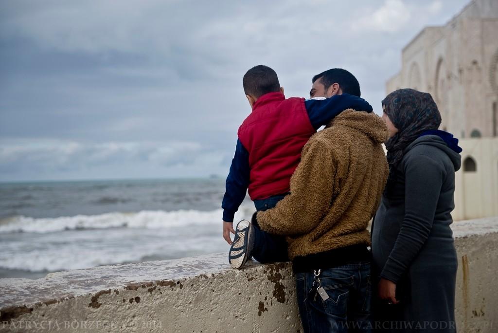 Rodzina muzułmańska podziwia fale nadchodzące z oceanu. Za nimi widać fragment meczetu.