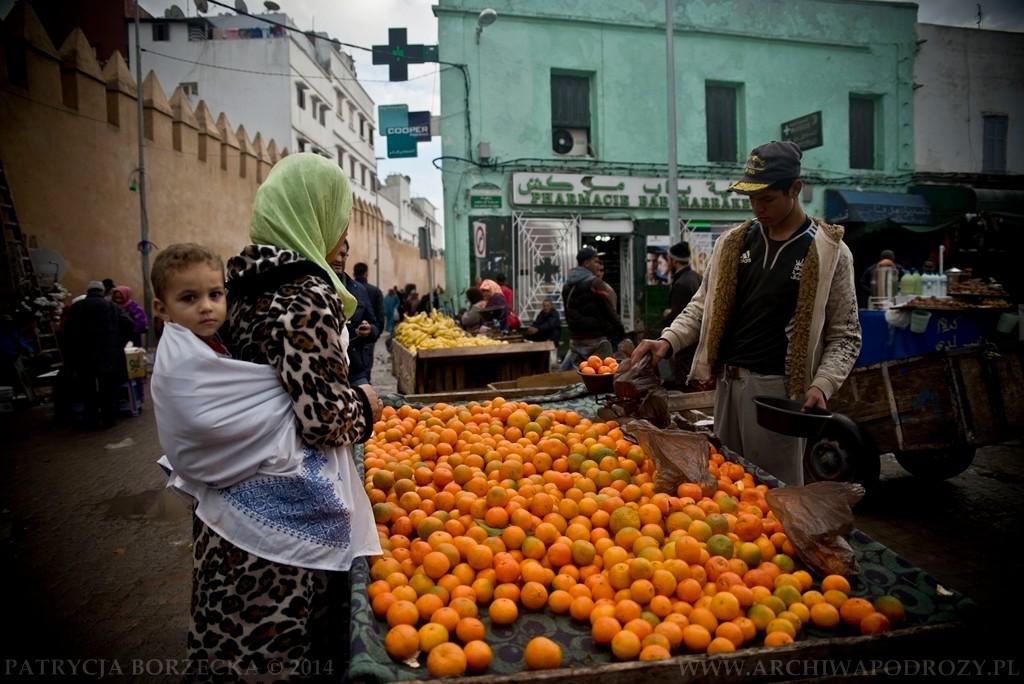 Kobieta z dzieckiem kupuje owoce. A sprzedawca cieszy się, że może zrobić tego dnia większy utarg bo w dzielnicy pojawiło się kilku białych.