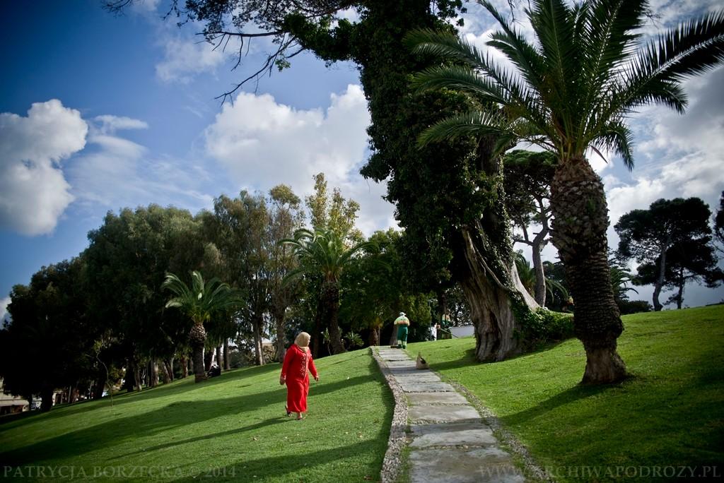 Park niedaleko tangerskiej mediny. Zieleń roślinności miesza się z czerwienią kobiecego ubrania.