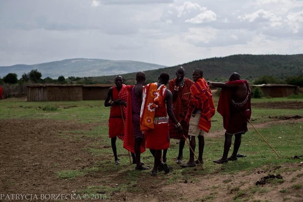 Grupa mężczyzn rozmawia między sobą i wskazuje na Mzungu, co jest określeniem na białego człowieka. Szybko zostaję zaproszona do rozmowy i bardzo uprzejmie powitana. Mam okazję przyjrzeć się bliżej życiu w wiosce. Na stopach Masajów widzę sandały zrobione z krowiej skóry. Niektórym z nich zdarza się czasem wkładać klasyczne sandały, które niejednokrotnie pochodzą z handlu wymiennego z białymi przybyszami.